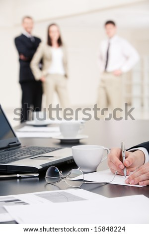 Vertical image of human hands making notes on paper on background of standing business people