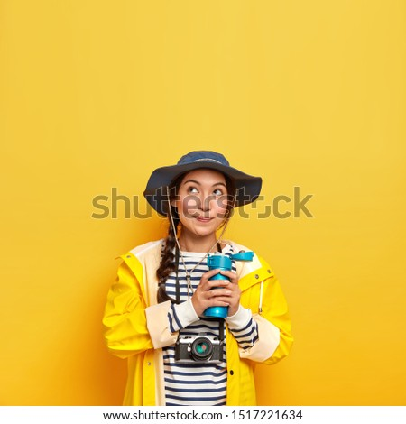 Vertical image of lovely thoughtful girl in stylish headgear, protective raincoat, holds thermos with hot drink, carries retro camera for making photographes, creats content for social media channel