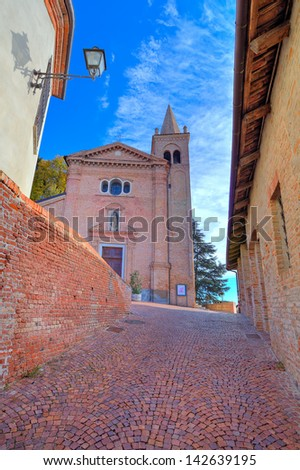 Vertical image of red brick church and narrow cobblestone street in at medieval part of the town in Monticello D'Alba, Italy. - stock photo