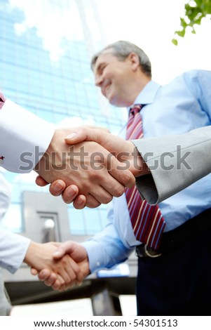 Vertical image of rows of partners handshaking outdoors on background of modern building