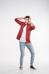 Vertical image of shocked man in shirt and jeans which holding head and looking away. Isolated white background