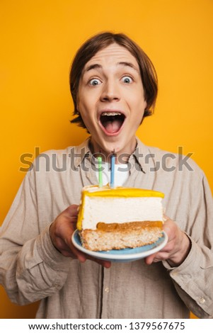 Vertical image of Surprised happy handsome man in shirt holding plate with cake and looking at the camera over yellow background