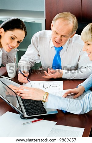 Vertical image of three business people sitting at the table and looking into the laptop monitor with one of businesswomen pointing at it with smile with some papers, pen and cup near by - stock photo