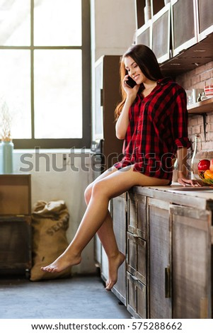 Vertical image of woman in red shirt with naked legs talking at phone and sitting on table in kitchen. Full length. Side view #575288662