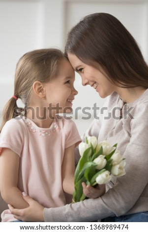 Vertical image small daughter and mom tender moment, family sitting together touching foreheads look at each other eyes celebrate eight march holiday, international womens day, happy birthday concept