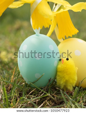 Vertical image: symbols of Easter festive: yellow little chick and Easter eggs are on green grass in a spring garden. #1050477923