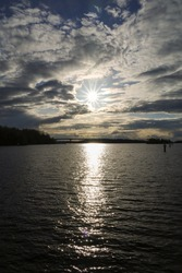 Vertical image with a lake, sun and scenic clouds. Sun rays and glare on the surface of the water