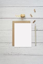 Vertical image with greeting card, invitation mockup for design presentation, kraft paper envelope, white wooden background.