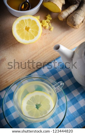 Vertical kitchen preparation scene containing ingredients for a honey, lemon and ginger drink - a herbal home remedy for the cold and flu season.