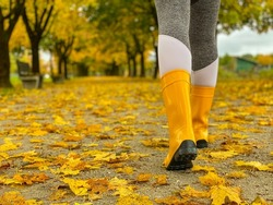 VERTICAL, LOW ANGLE, CLOSE UP, DOF: Unrecognizable young female explores the picturesque autumn colored park in November. Woman wearing yellow rubber boots walks along an avenue covered in leaves.