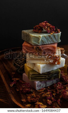 Vertical moody view of natural bar soaps with dry roses on black and wooden background.