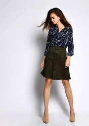 Vertical of a short beautiful cheerful young woman posing in solitude, in a dark silk blouse with floral patterns, a dark short green skirt with buttons and high-heeled shoes, looking away