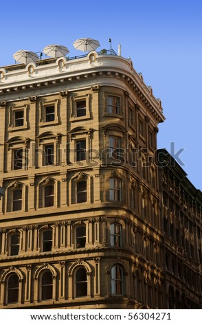 Vertical of several stories of an old posh hotel showing superb architecture details with rooftop terrace against the blue sky.