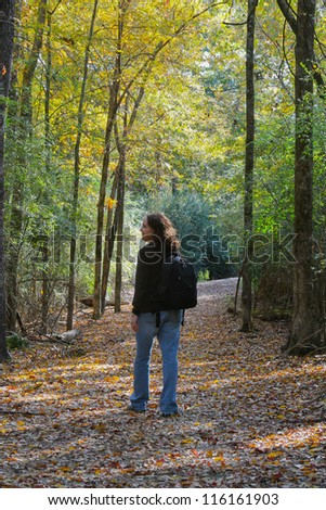 vertical orientation of a happy woman walking in the forest with fall colors and copy space / Autumn Day Hiker
