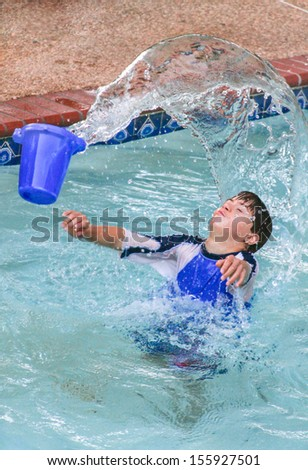 vertical orientation of boy with autism and down's syndrome outside in the pool playing with a bucket of water /  Sensory Splash Play