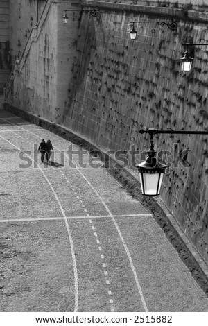 Vertical oriented image of couple walking on paved promenade along Tiber river in Rome, Italy.