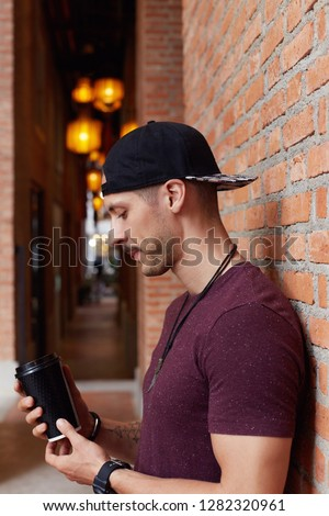 Vertical outdoor shot of serious bearded young expat male with tattooed arms, dressed casually, spends summer vacations in foreign country, having brake, rests against cafe interior with cup of coffee