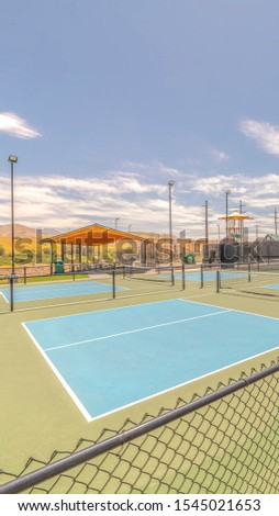 Vertical Outdoor tennis courts and sunny recreational park
