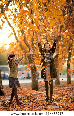 Vertical photo,  happy beautiful little girl with mather throw up  autumnal leafage, in park. Focus on little girl.