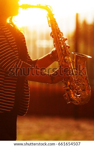 Vertical photo of a female sax player during sunset #661654507
