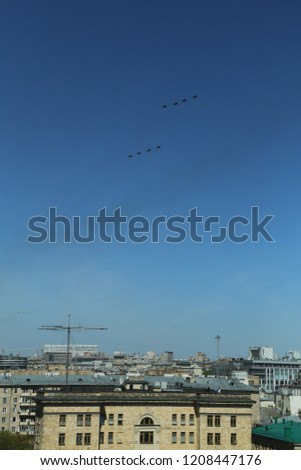 vertical photo of a group of eight russian military fighter jet planes flying in two rows formation high in blue sky at Vicotry Day parade air show on 9 May over roofs and building of Moscow, Russia