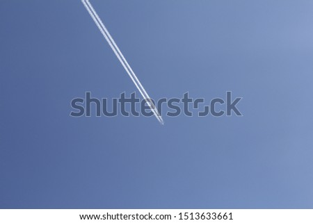 Vertical photo of a large white plane. A plane flies through the sky. The sky is blue. After the plane, a trace is visible.