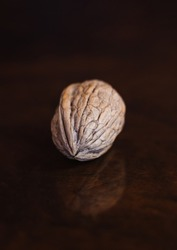 Vertical photo of a walnut on a reflective wood surface with the walnut reflected in symmetrical
