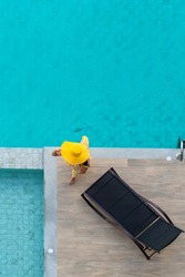 Vertical photo of Asian woman in yellow dress at the pool on a wooden pier shot with chaise-longue from above.