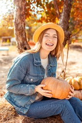 Vertical photo of attractive and happy young adult woman holding ripe, orange pumpkin in hands, looking at camera and sitting outdoor in denim jeans wear. Concept of autumn harvest on garden