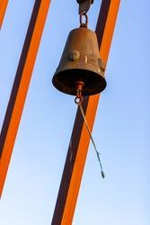 Vertical photo of bell of memorial for children lost in shipwreck of ferryboat Estonia moving in wind during sunset in sea on Tahkuna peninsula, Hiiumaa island, Moonsund archipelago, Estonia