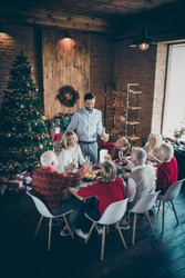 Vertical photo of big eight members family sit dinner table father guy telling x-mas toast multi-generation reunion in newyear atmosphere decor living room indoors
