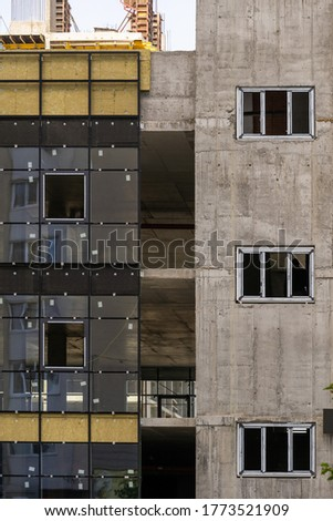 Vertical photo of building under construction with rock wool insulation on exterior, glass windows in concrete wall. Concept of new unfinished multistory