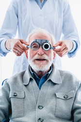 Vertical photo of cheerful elderly patient undergoing sight check with ophthalmic glasses
