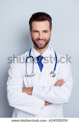 Vertical photo of cheerful smiling doctor standing with crossed hands against gray background