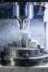 Vertical photo of industrial wet milling process in 5-axis cnc machine with coolant flow under pressure and freezed splashes