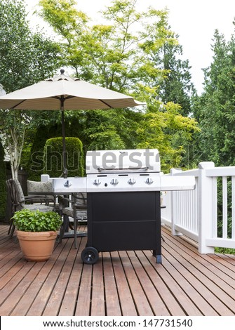 Vertical photo of large barbecue cooker on cedar deck with patio furniture and trees in background   #147731540