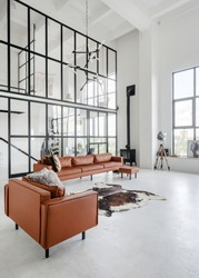 Vertical photo of living room at home with modern interior, fireplace near leather comfortable sofa, armchair, decor and skin carpet on concrete floor against glass wall on background