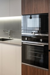 Vertical photo of modern built in appliance, electric oven, microwave and sink with chrome water tap in new contemporary kitchen at elegant house with stylish interior