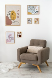 Vertical photo of modern living room in contemporary house with artworks in frame on brick wall, cushioned furniture, comfortable armchair and fur on floor