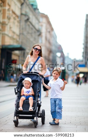 Vertical photo of mother with her son and toddler daughter in stroller walking in city center