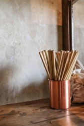 Vertical photo of natural color bamboo straws in rose gold bronze cup  on wooden table with loft concrete background