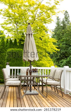 Vertical photo of outdoor patio table with cold bottled beer in bucket and drinking glasses on cedar wood patio. Colorful trees in background.