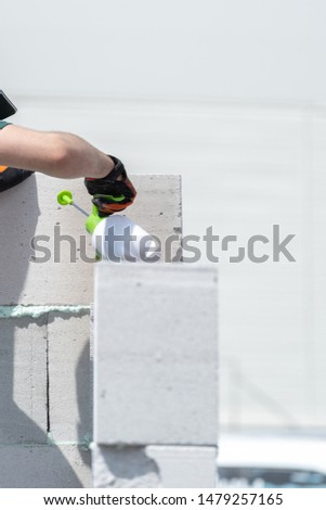 Vertical photo of qualified work man building new house wall from white gas silicate block. Mature male holding special water sprayer instrument in hands and wetting brick