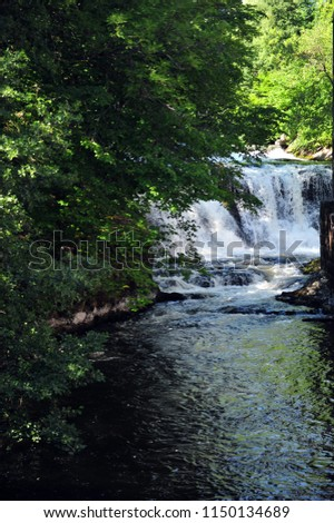 Vertical photo of river Akerselva in Oslo, Norway and small water falls.  Summer day.