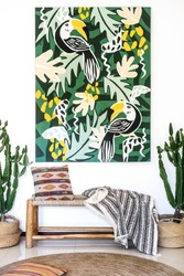 Vertical photo of room with cozy interior design, artwork painting on wall, bench seat, cushions, plaid, rug on floor and cactus plants in baskets