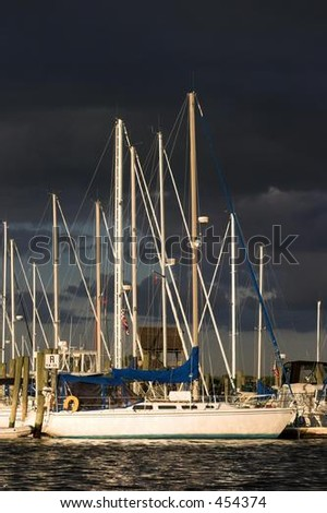 Vertical photo of sailboats in a Marina with dark clouds in the background. Mystic, Connecticut. - stock photo