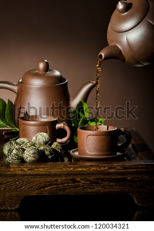vertical photo, of the clay teapot tea flow in  cup on brown background,  tea ceremony