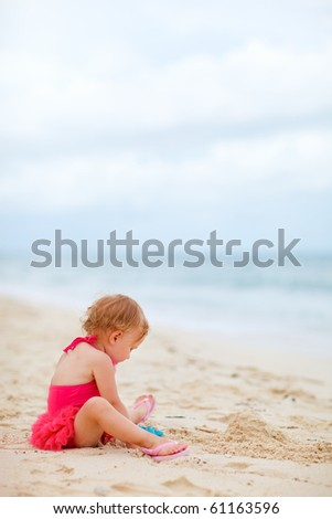 Vertical photo of toddler girl playing with toys at tropical beach