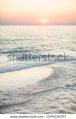 Vertical photo of tranquil tropical ocean at sunset, beautiful gentle calm ocean with pink sky reflection on the sea. Soft focus.