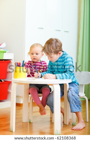 Vertical photo of two small kids drawing together at their room